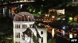 Papirne lampe plutaju rekom Motojasu iza osvetljene zgrade u blizini memorijalnog parka u Hirošimi