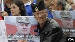 Para pendukung melakukan protes atas pengadilan Mladic dengan membawa poster Ratko Mladic.