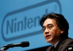 FILE - In this Jan. 31, 2013 file photo, Nintendo Co. President Satoru Iwata speaks during a news conference in Tokyo.