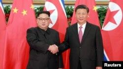Lãnh tụ Bắc Hàn Kim Jong Un bắt tay với Chủ tịch Trung Quốc Tập Cận Bình tại Đại Liên, Trung Quốc.