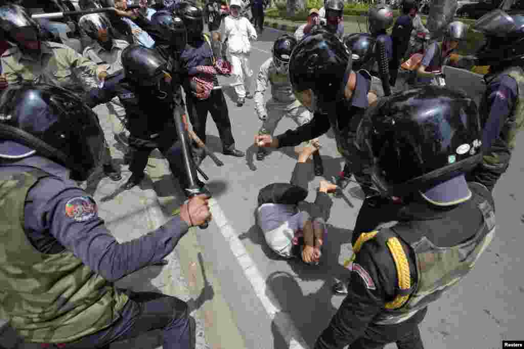 A man tries to protects himself as security forces beat him during the International Workers' Day rally at Freedom Park in Phnom Penh, Cambodia. Authorities broke up a protest of garment workers and opposition party supporters who rallied to celebrate the Labor Day despite the government's ban on public assemblies.