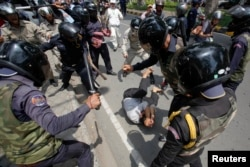 FILE - Security forces beat a man during an International Workers' Day rally in Phnom Penh, May 1, 2014. Authorities broke up a protest of garment workers and opposition party supporters who were marking the event despite a ban on public assemblies.