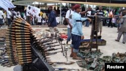 An October 2009 photo shows Nigerian militant youths displaying weapons surrendered by former militants at an arms collection center in the oil hub Port Harcourt.