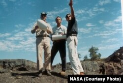 Astronauts Edgar Mitchell and Alan Shepard being guided by a NASA geologist at Craters of the Moon before their lunar mission in 1969.
