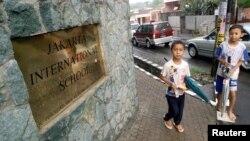 Dua orang anak ojek payung di depan kampus Jakarta International School.
