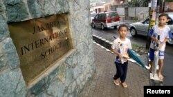 Hai cậu bé Indonesia đứng trước cổng trường Quốc tế Jakarta.