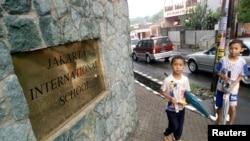 Dua anak laki-laki melewati bagian depan Jakarta International School.