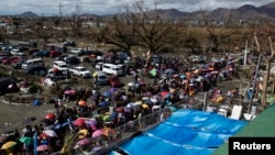 Residentes de Tacloban procuram lugar a bordo dos aviões que chegam com ajuda a cidade praticamente destruída pelo tufão Haiyan, para fugir para Manila (13 Nov. 2013)
