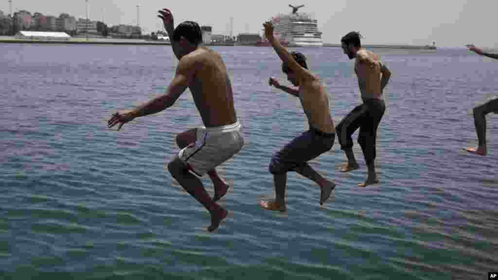Des Afghans sautent dans la mer dans le port d'Athènes, où des centaines de réfugiés et de migrants vivent, le 20 juin 2016.