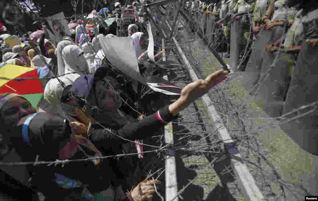 Female members of the Muslim Brotherhood and supporters of ousted Egyptian President Mohamed Morsi shout slogans at a barbed wire fence near the Defense Ministry in Cairo, July 21, 2013.