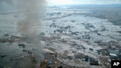 Fires burn in a harbor following an earthquake and tsunami in Natori City, Miyagi Prefecture, northeastern Japan, March 11, 2011