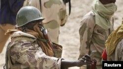 Un soldat nigérien couvre son visage tout en prenant une photo d'une fosse commune dans la ville de Damasak, au Nigeria, 20 mars 2015. REUTERS / Emmanuel Braun - RTR4U97T