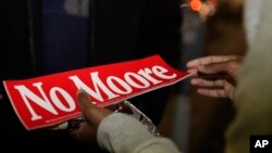 "Tori Sisson, right, receives a gift of chocolate and a ""No Moore,"" sticker, named after Roy Moore, from a supporter, near the Montgomery County Courthouse Sunday, Feb. 8, 2015."