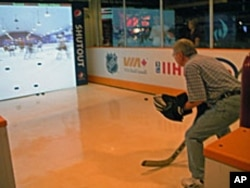 A visitor tries this state-of-the-art interactive exhibit where he is in the net and trying to stop simulated shots from NHL legends like Wayne Gretzky and Mark Messier