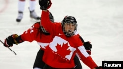 Canada's Meghan Agosta-Marciano celebrates after scoring what turned out to be the game-winning goal on Team USA's goalie Jessie Vetter (not shown) during their women's ice hockey game at the Sochi Winter Olympics, Feb.12, 2014.