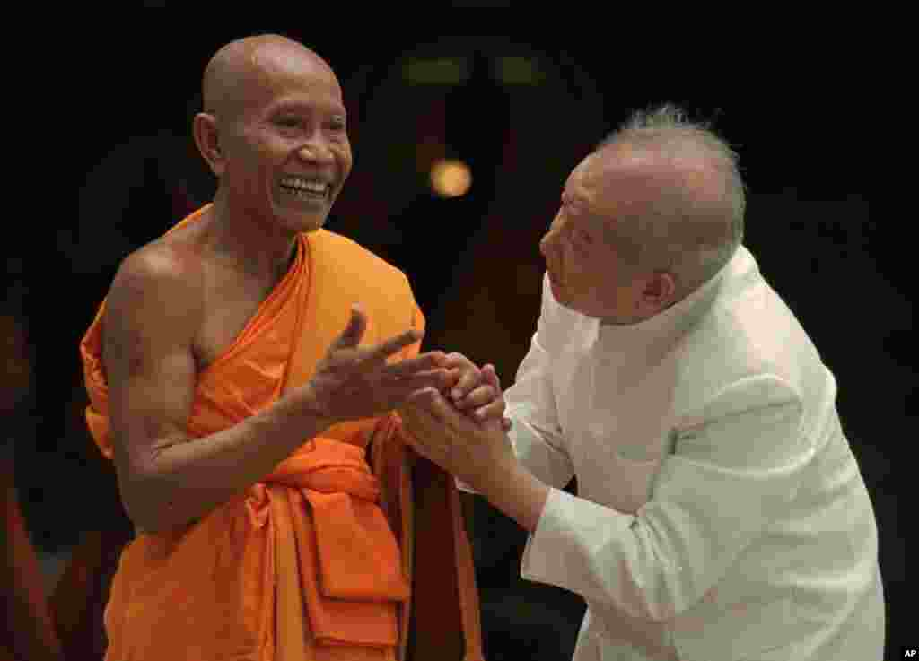 Cambodian King Norodom Sihanouk bids goodby to a Buddhist monk at a temple in Siem Reap, in northern Cambodia, on September 1, 1997.