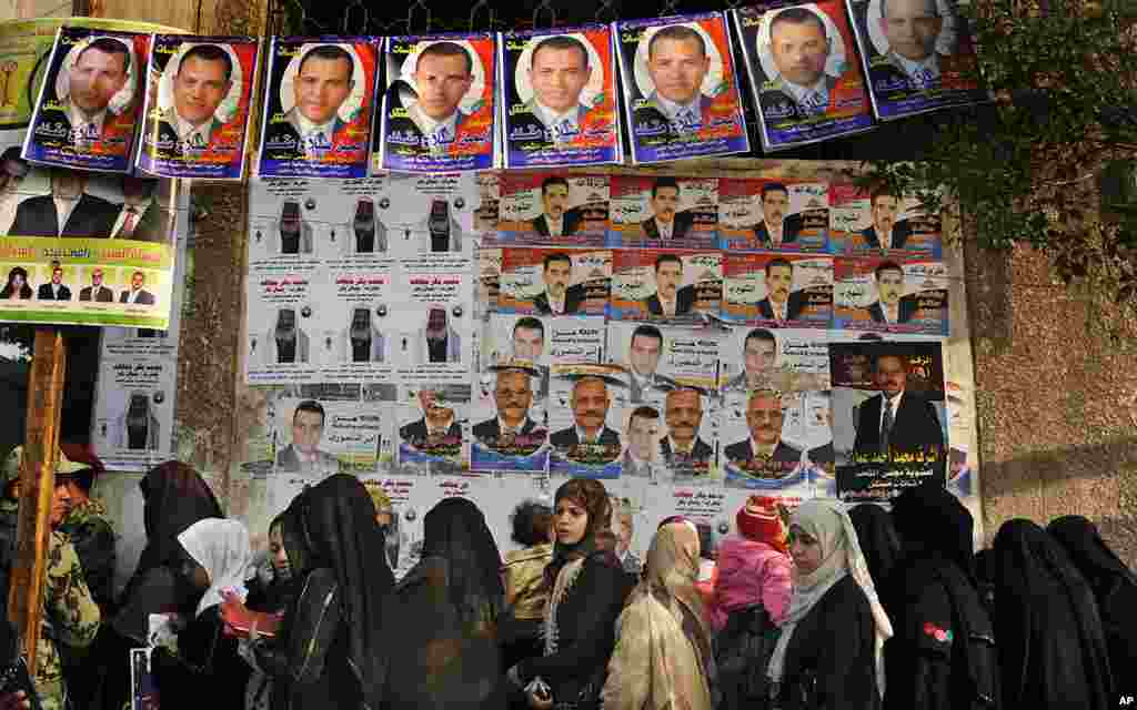Egyptian women line up in front of election posters for candidates before entering a polling station in Cairo, November 29, 2011. (AP)