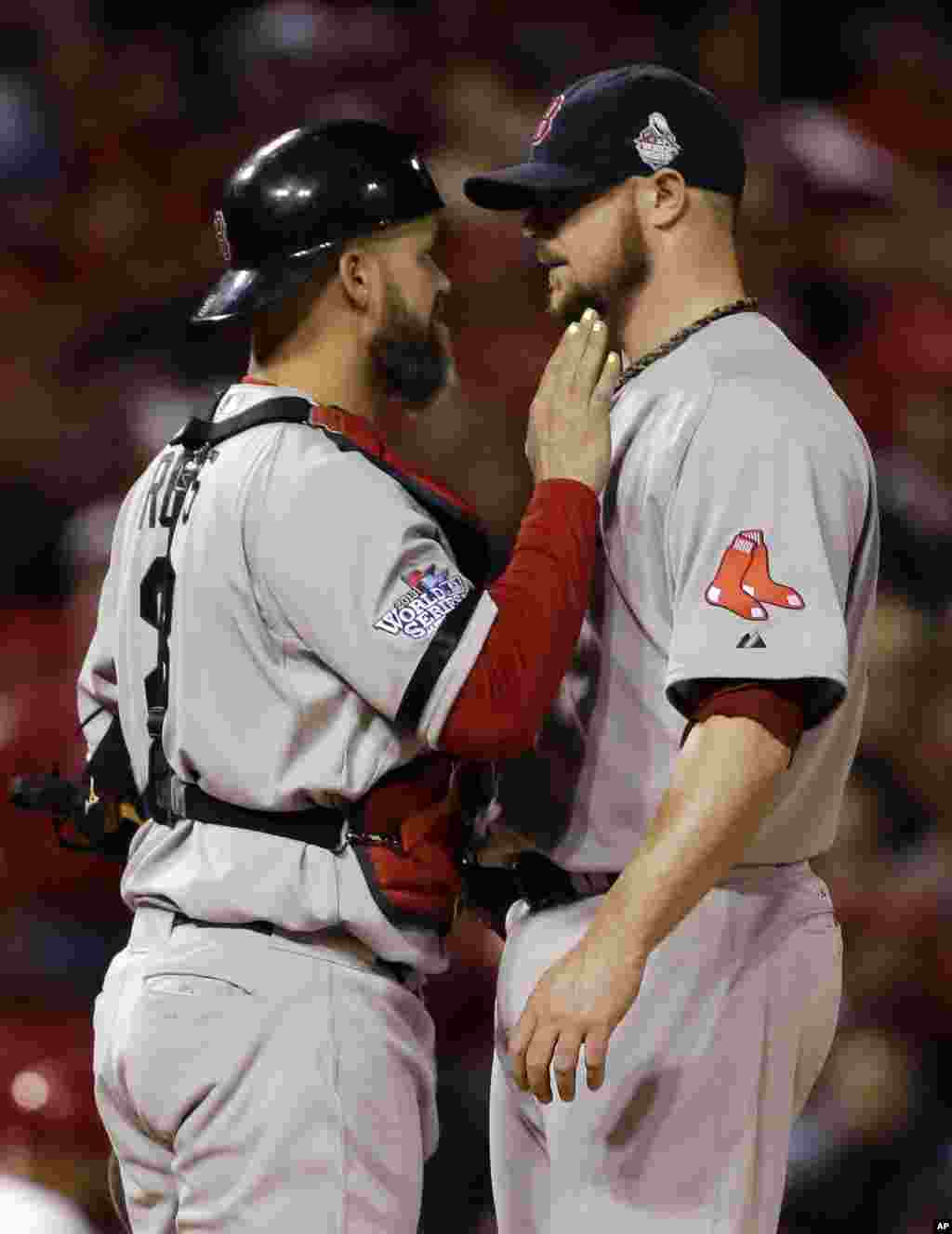Boston Red Sox catcher David Ross talks to starting pitcher Jon Lester during the eighth inning of Game 5 of baseball's World Series against the St. Louis Cardinals, Oct. 28, 2013.
