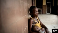Rachel Sakie (16) and her daughter Isaatu (15 months) await for consultation at the Star of the Sun Health Center in the Monrovia township of West Point, Liberia, April 29, 2016.