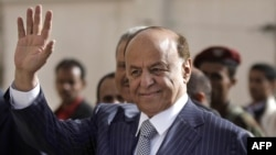 FILE - Yemen's then Vice President Abed Rabbo Mansour Hadi waves as he enters a polling center in 2012. There are conflicting reports about the whereabouts of Hadi, who is now Yemen's president.