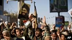 Un rebelle chiite connu comme un Houthi, deuxième à gauche, tient une affiche du chef du Hezbollah, cheikh Hassan Nasrallah alors qu'il assiste avec ses camarades une manifestation pour dénoncer l'agression Arabie à Sanaa, au Yémen, le 22 Avril 2015.