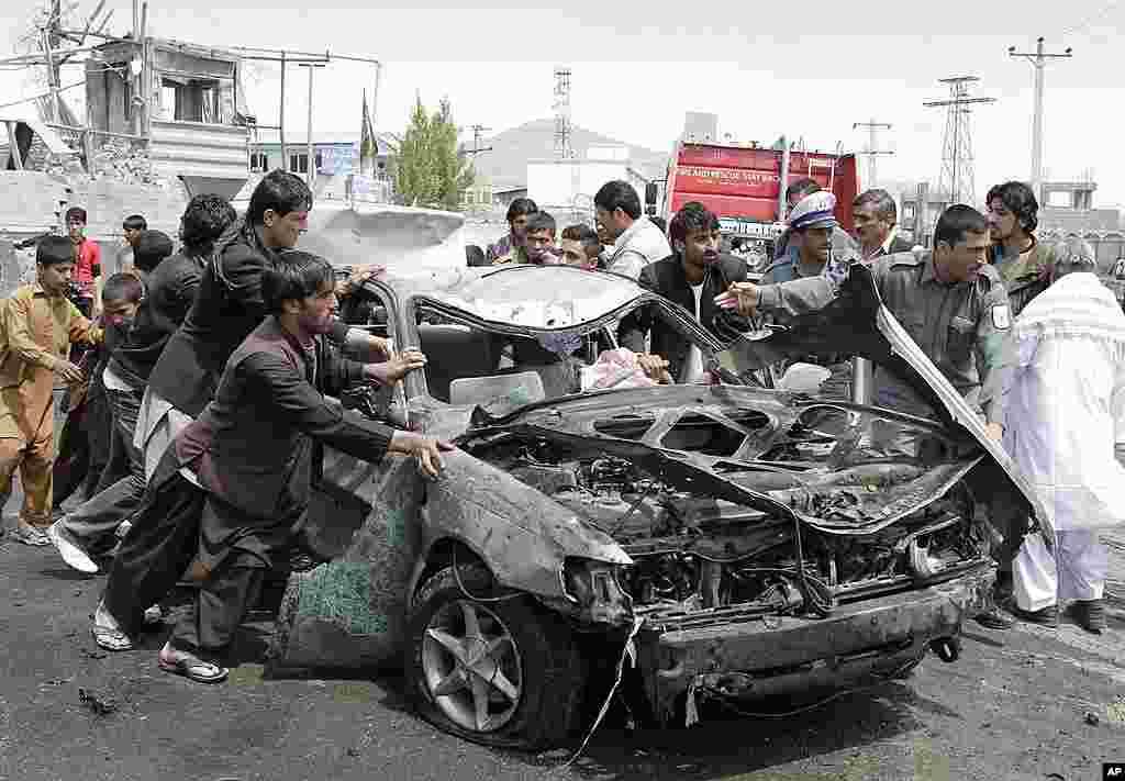 Un grupo de peatones ayudan a empujar un auto afectado por la explosión ocurrida en Kabul, Afganistán. (AP Photo/Ahmad Jamshid)