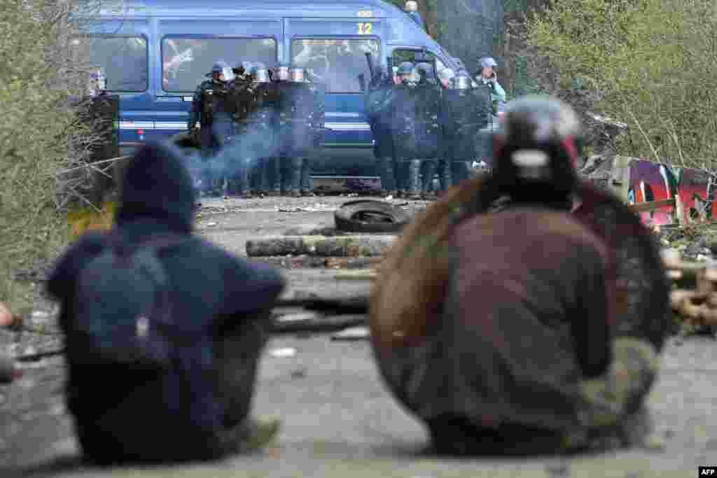 프랑스 노트르담데랑드에 있는 개발지연구역(ZAD)에서 국가헌병대원들이 불법 거주자들을 강제 퇴거시키기 위해 10년 전 지어진 캠프 철거에 착수했다. 강제 퇴거를 거부하는 시위대원들이 국가헌병대원들을 바라보고 있다.