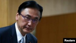 FILE- Japan's Minister-in-Charge of the Abduction Issue and head of the national public safety commission Keiji Furuya arrives at a meeting with the family members of victims kidnapped by North Korea, in Tokyo May 30, 2014.