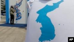 一名女士在朝鮮半島地圖上貼上祝願和平的訊息