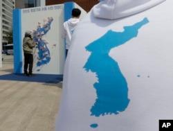 一名韩国妇女在首尔张贴的朝鲜半岛地图上贴上祈祷和平的字条。 (2016年4月26日)