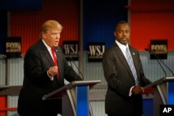 FILE - Donald Trump speaks as Ben Carson listens during the Republican presidential debate at the Milwaukee Theatre, Nov. 11, 2015, in Milwaukee