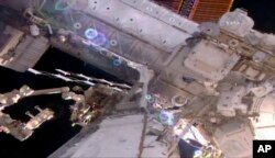 This still image taken from live video provided by NASA shows astronaut Shane Kimbrough, right, working on the International Space Station during a space walk, March 24, 2017.