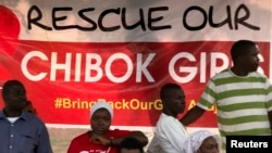 "Protesters from the remote town of Chibok stand next to a poster reading ""Rescue our Chibok girls,"" at a protest calling for the release of abducted schoolgirls, in Abuja, Nigeria, May 16, 2014."