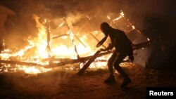 """A migrant is seen in silhouette near flames from a burning makeshift shelter on the second day of the evacuation of migrants and their transfer to reception centers in France, as part of the dismantlement of the camp called the """"Jungle"""" in Calais, France, Oct. 25, 2016."""
