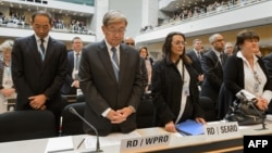 Delegate stands for a minute of silence in memory of the deceased health workers at the World Health Organization (WHO) assembly, May 18, 2015, Geneva.