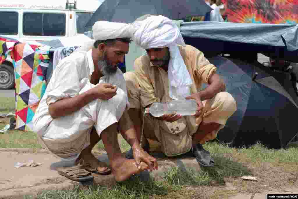 طاہر القادری کی امامت میں نماز جمعہ کے لیے لوگ وضو کر رہے ہیں۔