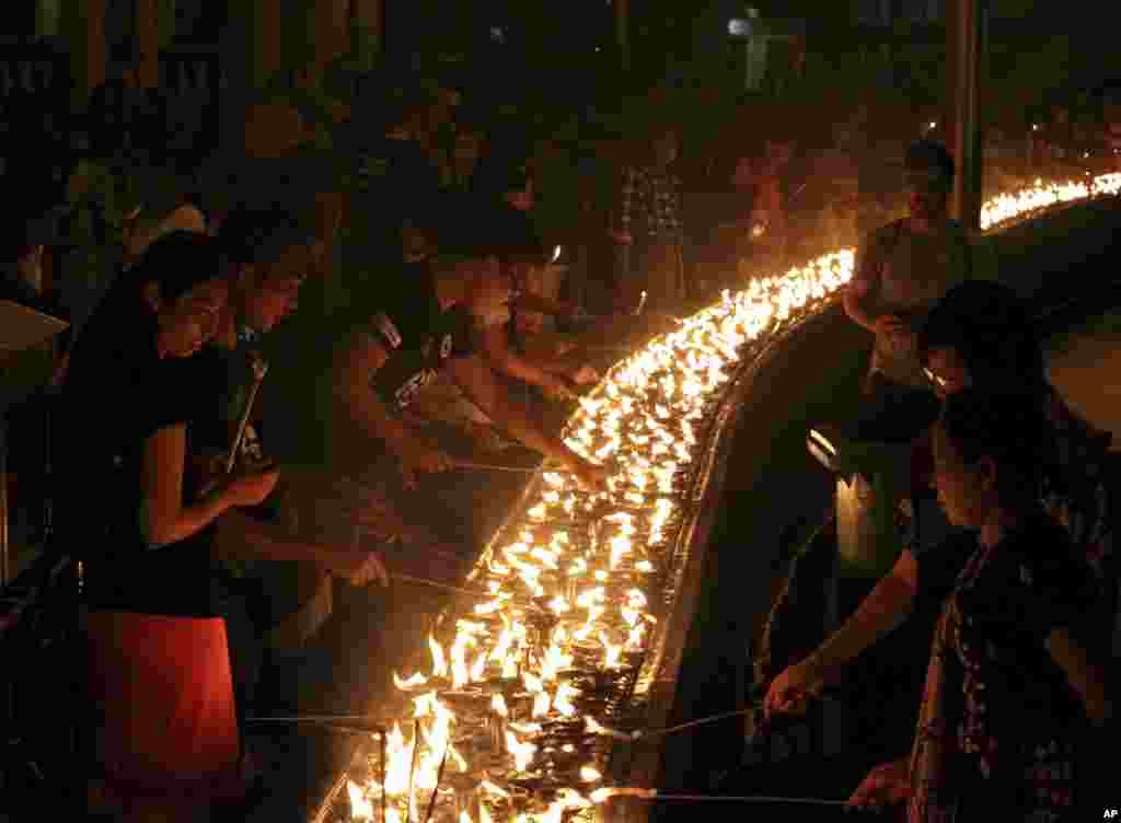Volunteers light oil lamps during earth hour celebrations at Myanmar's famous Shwedagon pagoda, in Yangon, Myanmar, March 25, 2017. Volunteers took part in earth hour celebrations organised by World Wide Fund for Nature (WWF-Myanmar) for the first time in