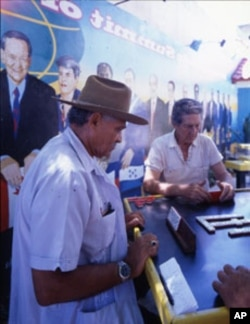 Men play dominoes next to a mural depicting the first Summit of the Americas, at which leaders of 34 North, Central and South American nations gathered in Miami in 1994.