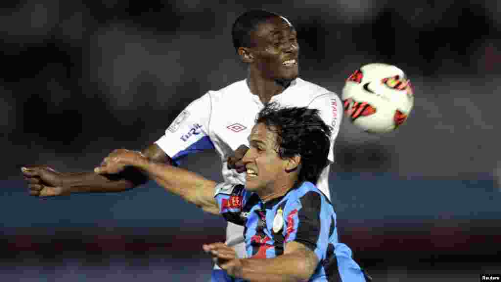 Victor Ferreira (front) of Peru's Real Garcilaso competes for the ball with Efrain Cortes of Uruguay's Nacional during their Copa Libertadores soccer match in Montevideo, May 9, 2013.