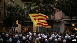 People wear white masks in support of Catalonian politicians jailed on charges of sedition and condemning the arrest of Catalonia's former president, Carles Puigdemont, in Germany, during a protest in Figures, Spain, April 5, 2018.