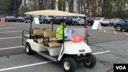 资料照片:在马里兰州在一家社区学院校园开设的大型新冠疫苗接种站的停车场,工作人员驾驶电瓶车接送行走不便的民众。(2021年4月12日)