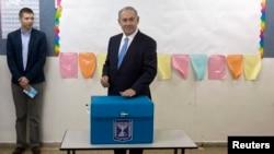 Le Premier minstre sortant israëlien Benjamin Netanyahu place son bulletin de vote dans l'urne pour les élections législatives en Israël, à Jérusalem, mardi 17 mars 2015.