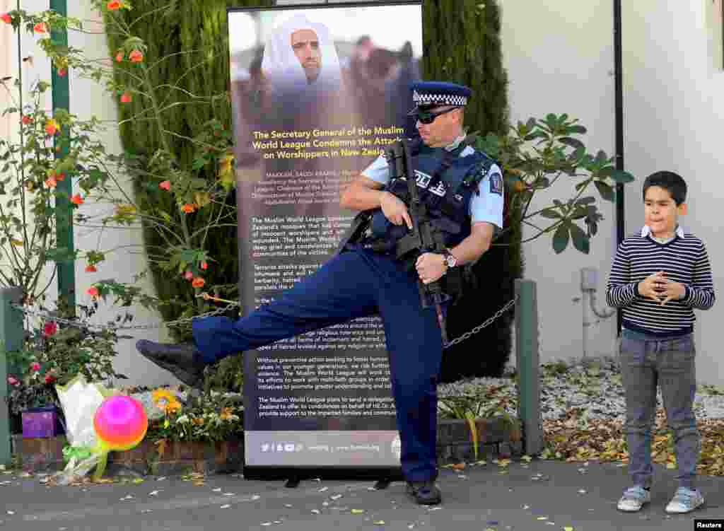 A police officer joins in a children's ball game as they wait for Britain's Prince William to finish his visit at Masjid al Noor in Christchurch, New Zealand.