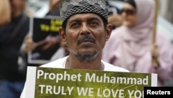 A Muslim protester holds up a sign during a protest against an anti-Islam film made in the U.S. mocking the Prophet Mohammad, outside the U.S embassy in Jakarta, September 21, 2012.