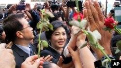 Mantan PM Thailand Yingluck Shinawatra (tengah) berjalan melewati para pendukungnya saat meninggalkan Mahkamah Agung Thailand di Bangkok (19/5).