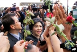 FILE - Thailand's former Prime Minister Yingluck Shinawatra, center, walks through supporters as she leaves the Supreme Court in Bangkok, Thailand, Tuesday, May 19, 2015.
