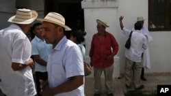 In this Dec. 17, 2017 photo, men wearing traditional Panamanian pintao hats leave Sunday Mass in La Pintada, Panama. (AP Photo/Arnulfo Franco)