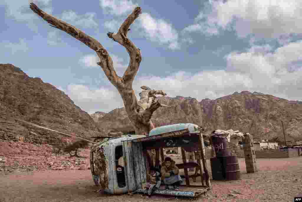 Egyptian Bedouin children sit on the rusted remains of a truck in the village of al-Hamada in Wadi el-Sahu in South Sinai governorate.