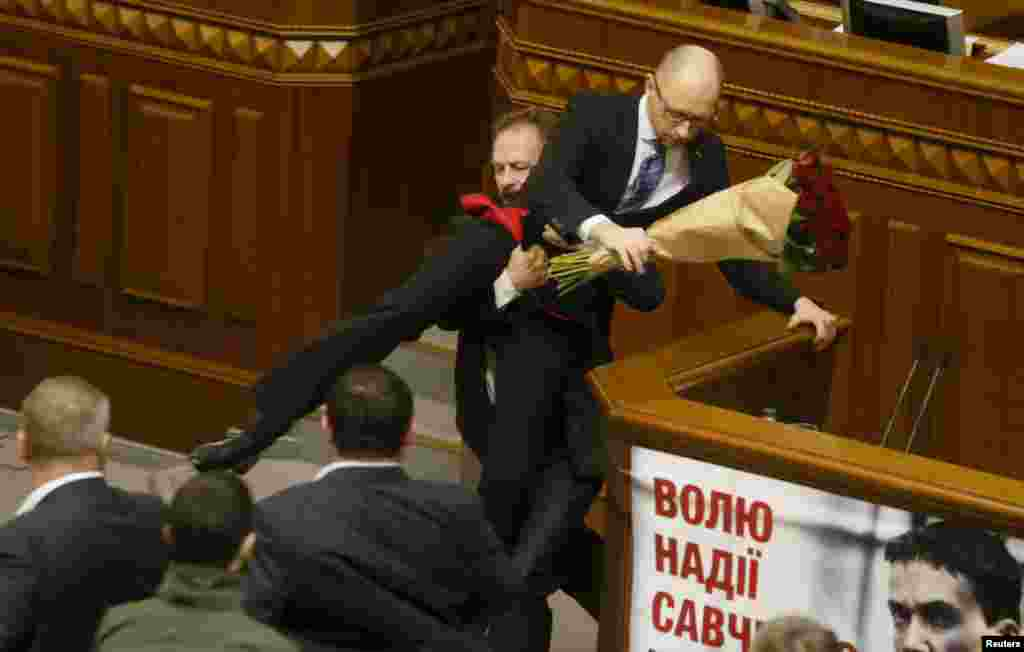 Rada deputy Oleg Barna removes Ukrainian Prime Minister Arseny Yatseniuk from the podium, after presenting him a bouquet of roses, during a session of parliament in Kyiv. Other Rada deputies scuffled with their colleague Barna immediately after the incident.