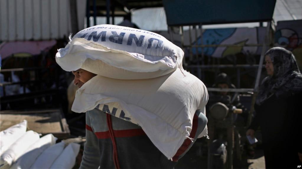 Palestinians receive food aid at a U.N. warehouse in the Shati refugee camp, Gaza City, Jan. 14, 2018.